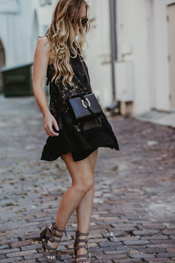 Shannon Jenkins of Upbeat Soles styles a casual boho summer outfit with Free People black lace dress, Dolce Vita Layell sandals, and Sancia crossbody bag