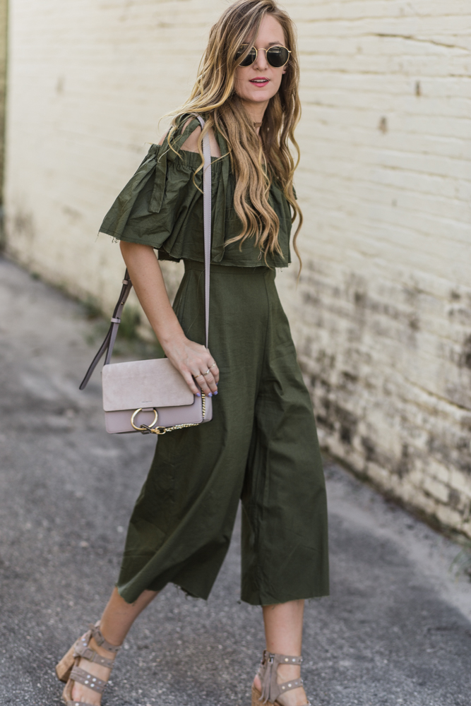 Shannon Jenkins of Upbeat Soles styles summer date night outfit ASOS olive culotte jumpsuit, studded Dolce Vita sandals, Amazon grey bag, and round Ray Bans