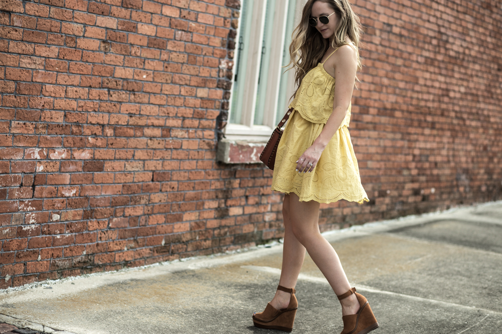 Shannon Jenkins of Upbeat Soles styles a summer weekend outfit with Chichwish yellow eyelet dress, Schutz wedges, and Rebecca Minkoff crossbody bag