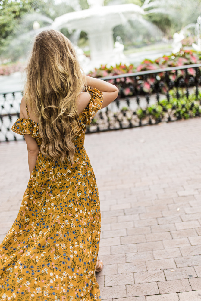 Shannon Jenkins of Upbeat Soles styles a summer date night outfit with Shein mustard floral maxi dress, Dolce Vita lace up sandals, and Rebecca Minkoff bag