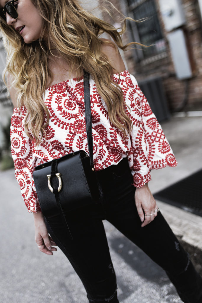 Shannon Jenkins of Upbeat Soles styles edgy summer outfit with red off the shoulder top, black flared jeans, and Sancia crossbody bag