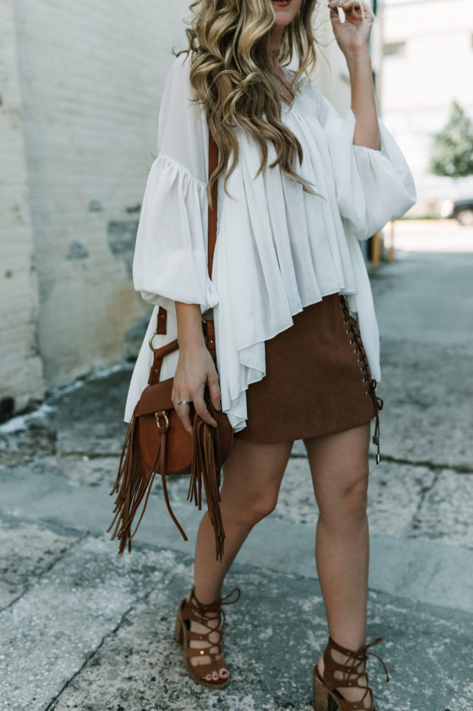 Shannon Jenkins of Upbeat Sole styles a cute fall transition outfit with lace up suede skirt, flowy chiffon top, an Dolce Vita lace up block heel sandals