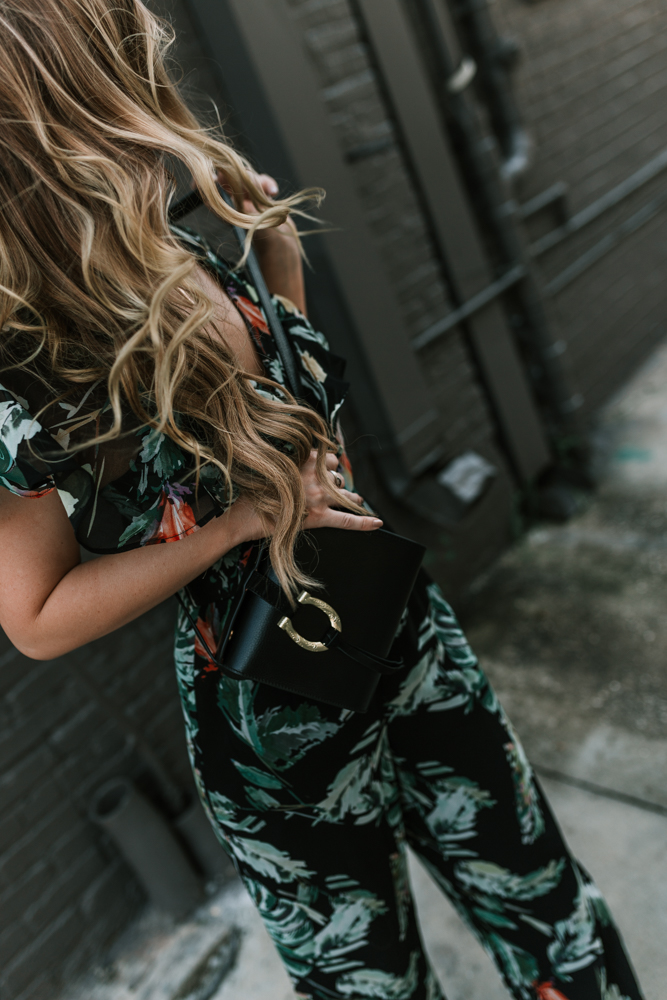 Shannon Jenkins of Upbeat Soles styles a Fall date night outfit with black floral jumpsuit, BlankNYC leather jacket, and Ray Ban clubmaster
