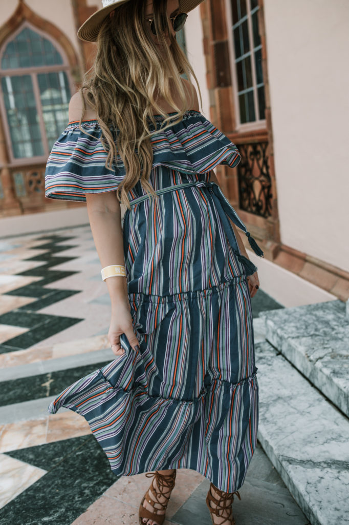 Shannon Jenkins of Upbeat Soles styles a cute vacation outfit with ASOS stripe and ruffle maxi dress, Dolce Vita lace up block heels, and gold choker