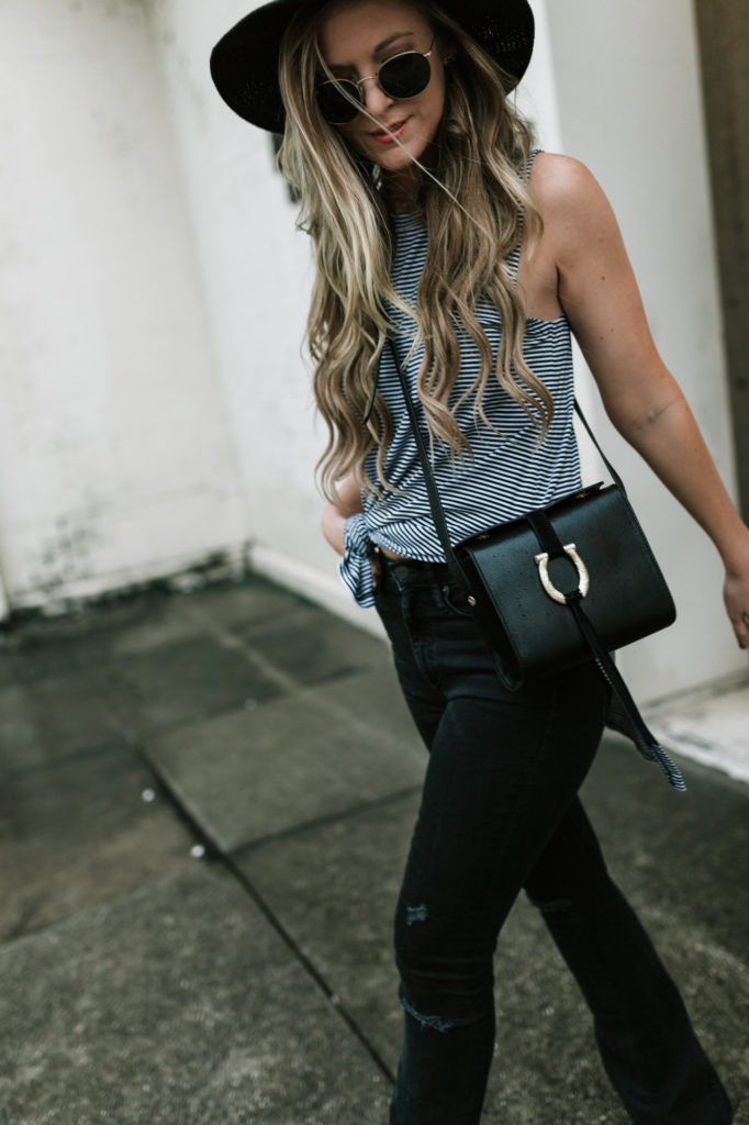 Shannon Jenkins of Upbeat Soles styles and edgy fall transition outfit with black flared jeans, BCBG striped tank, Sancia crossbody bag, Baublebar choker
