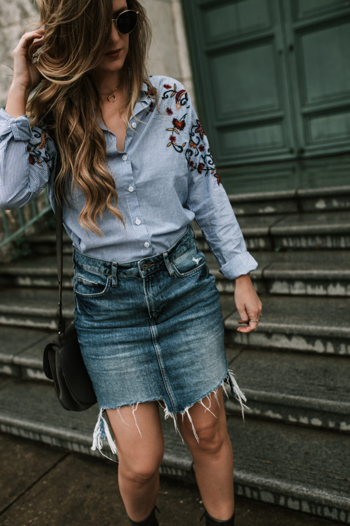 Shannon Jenkins of Upbeat Soles styles a fall transition outfit with embroidered striped button up shirt, frayed denim skirt, and metallic booties