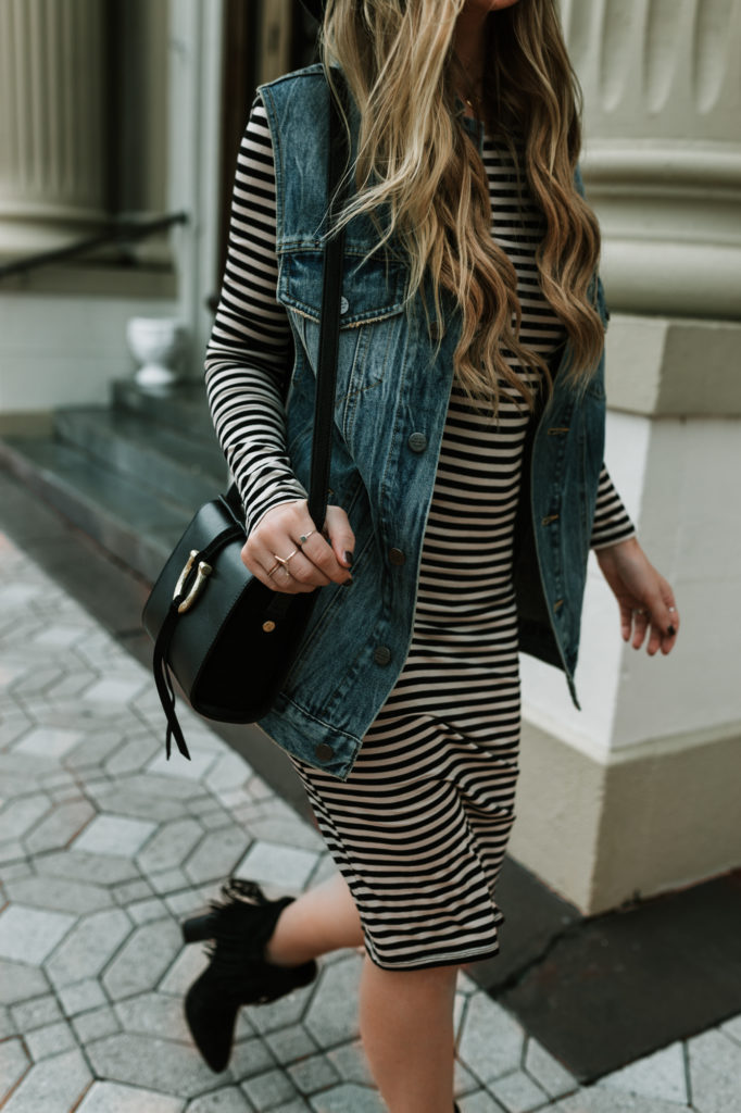 Shannon Jenkins of Upbeat Soles styles a fall transition outfit with striped long sleeve midi dress, oversized denim vest, and suede fringe booties