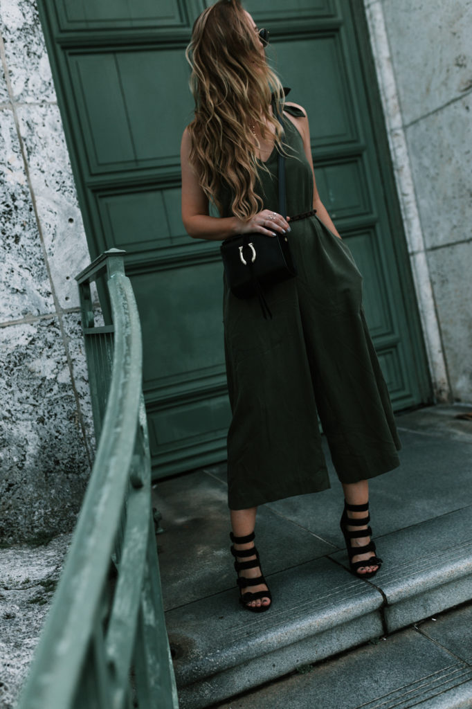 Shannon Jenkins of Upbeat Soles styles fall date night outfit with olive culotte jumpsuit, black buckle heels, Sancia crossbody bag, and round Ray Bans