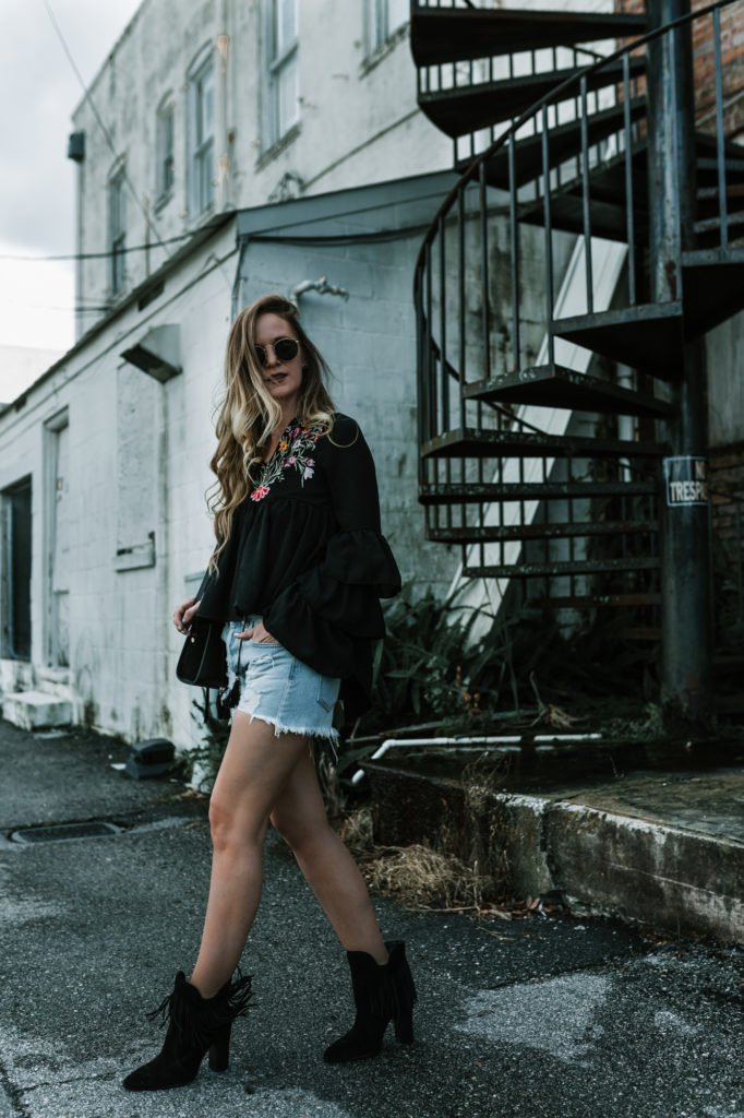 Shannon Jenkins from Upbeat Soles wears a boho fall transition look in an embroidered top with distressed denim jean shorts and fringed booties
