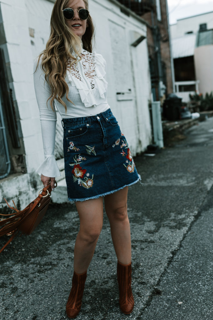 Shannon Jenkins of Upbeat Soles styles a fall date night outfit with embroidered denim skirt, ruffled bodysuit, and fringe crossbody bag