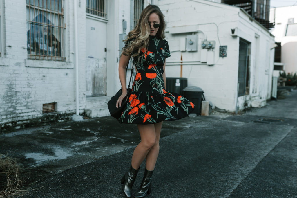 Shannon Jenkins from the budget friendly fashion blog Upbeat Soles wears a cute backless rose print dress with metallic booties