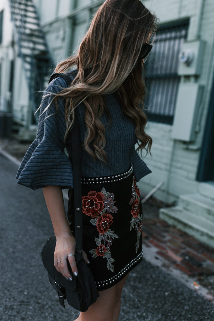 Shannon Jenkins from the Florida Fashion Blog Upbeat Soles styles an edgy date night outfit with embroidered skirt, bell sleeved sweater and leather booties