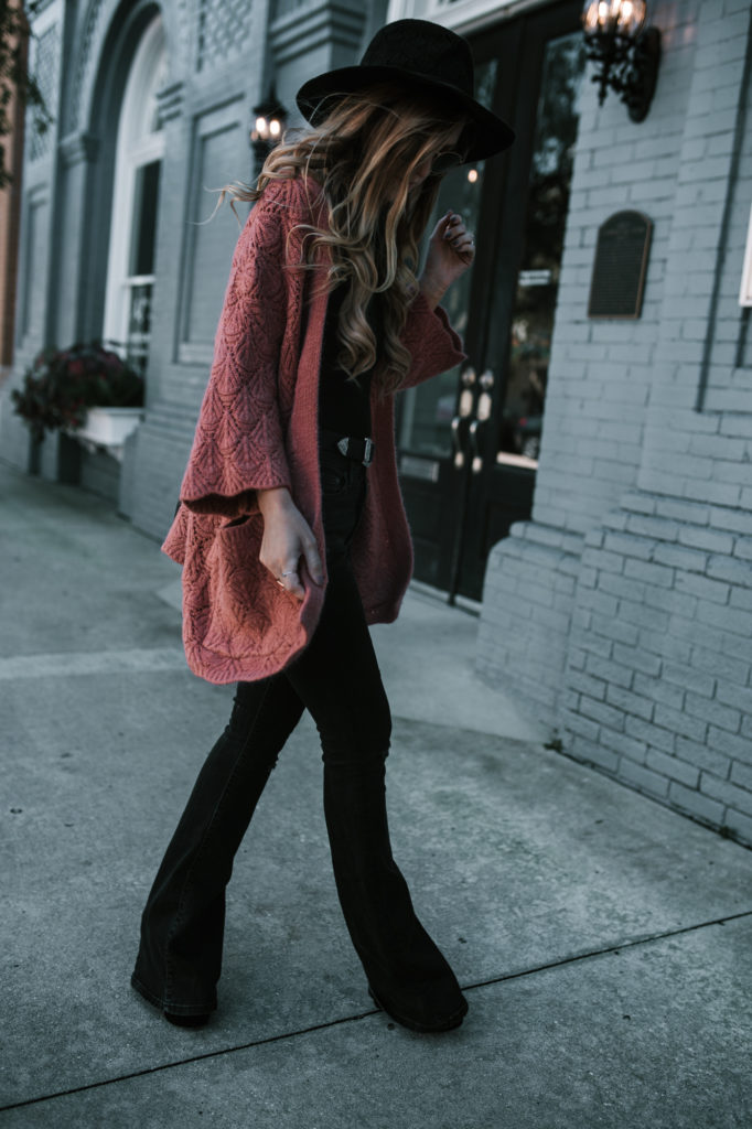 Shannon Jenkins from Upbeat Soles styles a fall weekend outfit with Chicwish coral cardigan, black high waisted denim flares and black hat