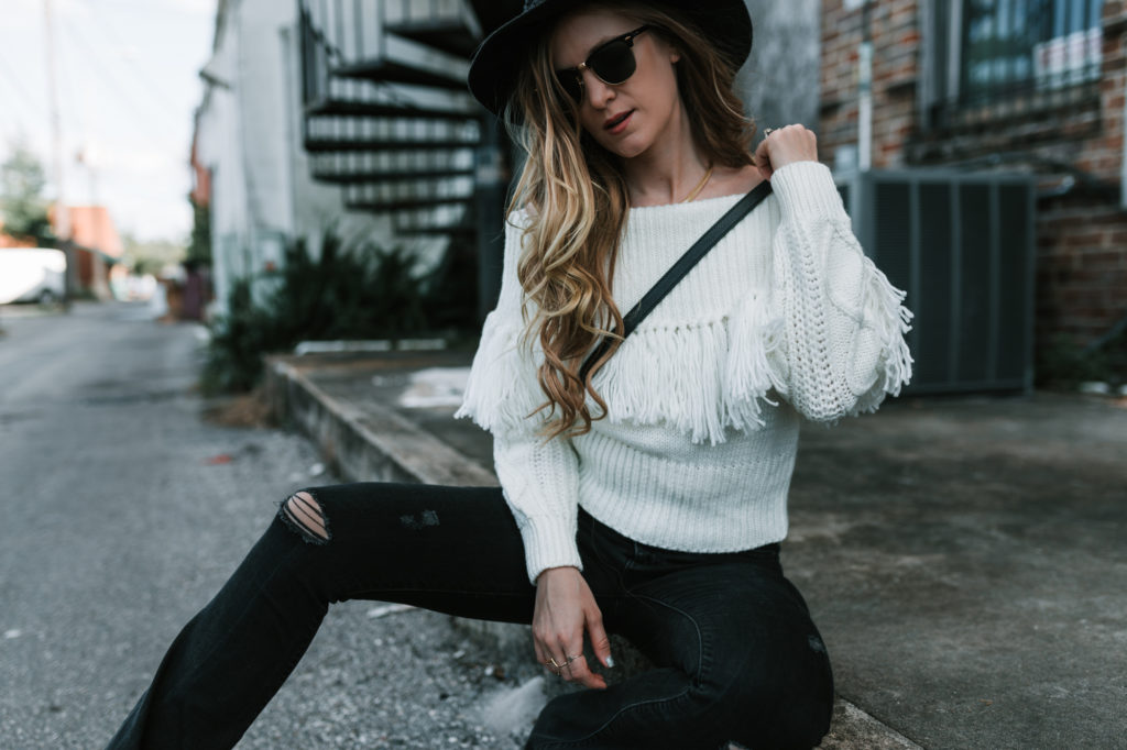 Shannon Jenkins from Upbeat Soles styles a white fringe sweater from Chicwish with black high waisted flared jeans for a boho outfit