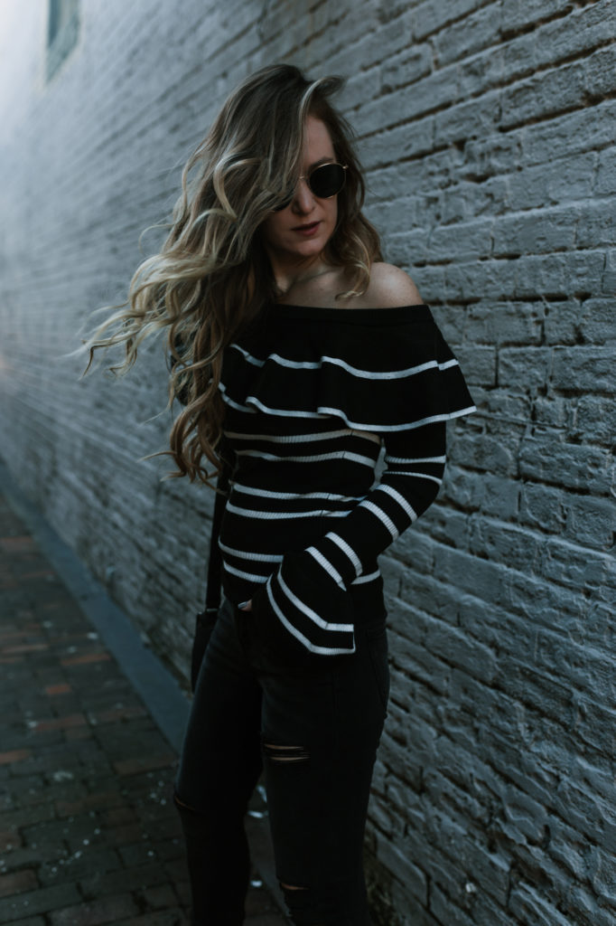Shannon Jenkins from the fashion blog Upbeat Soles styles an Akira off the shoulder sweater with some distressed Hidden Jeans