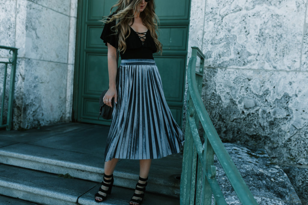 Shannon Jenkins from Florida fashion blog Upbeat Soles styles a velvet pleated skirt from Chichwish with black heeled sandals and round Ray Ban Sunglasses