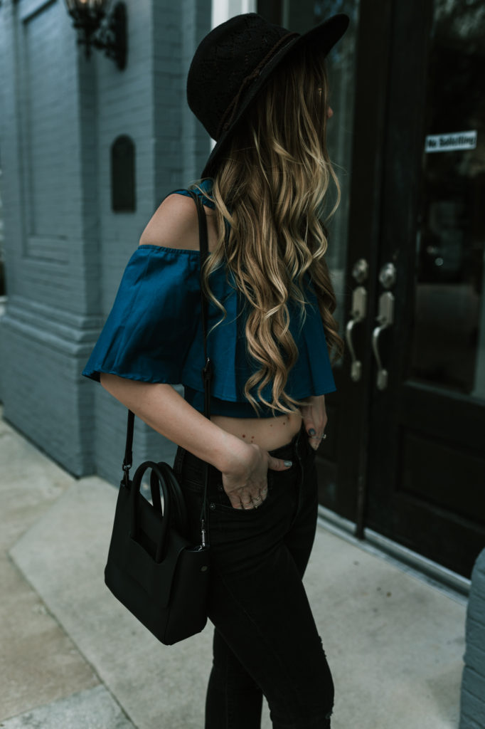 Shannon Jenkins from Budget Friendly Fashion Blog styles an open shoulder crop top with high rise black jeans