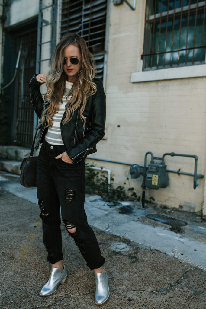 Shannon Jenkins of Upbeat Soles styles a leather jacket outfit with black distressed boyfriend jeans, Kelsi Dagger silver booties, and Ray Ban sunglasses