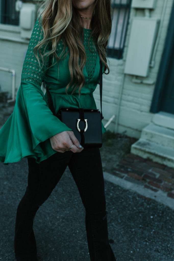 Shannon Jenkins from the budget friendly fashion blog Upbeat Soles styles a holiday green top from Shein with highwaisted denim flares