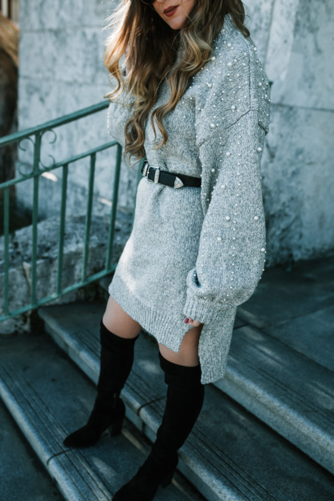 Shannon Jenkins of Upbeat Soles styles an oversized sweater dress outfit with pearl details, Dolce Vita over the knee boots, and double buckle belt