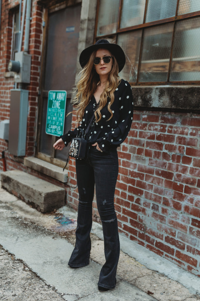 Shannon Jenkins of Upbeat Soles styles a boho winter outfit with black flared jeans, polka dotted lace up blouse, Rebecca Minkoff jewel bag, and Ray Bans