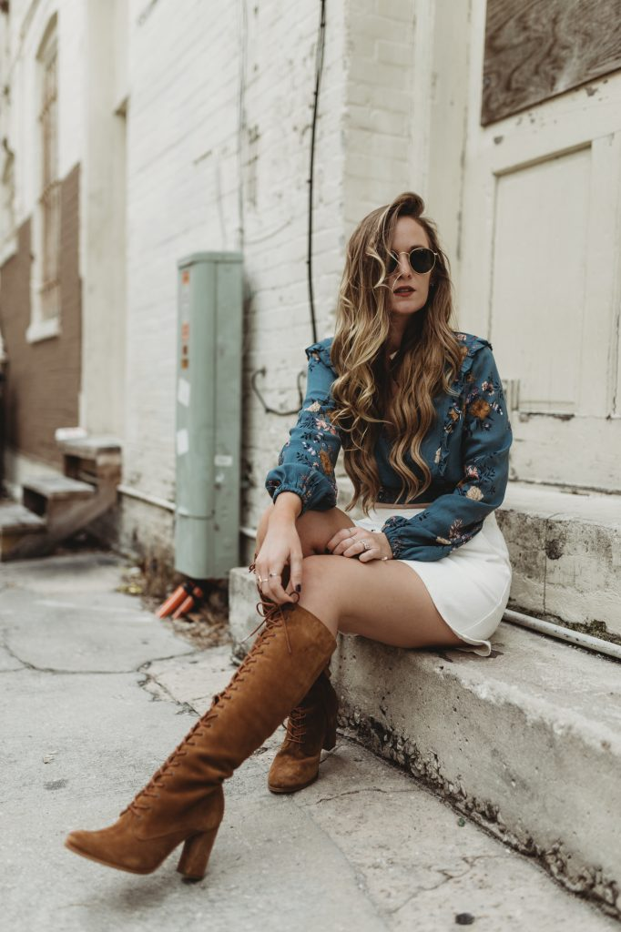 Shannon Jenkins of Upbeat Soles styles a spring boho outfit from The Label Orlando with a floral crop top, lace up denim skirt, and Matisse lace up suede boots