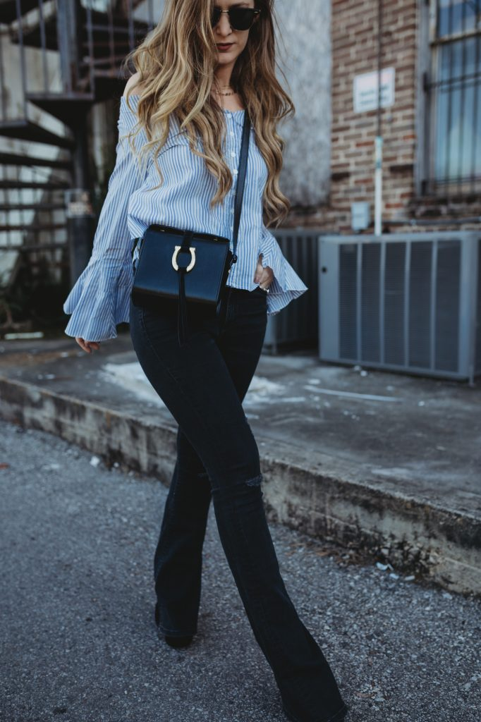 Shannon Jenkins from fashion blog Upbeat Soles styles a black flared jeans outfit with a with a bell sleeved top from Free People