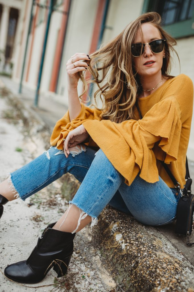 Shannon Jenkins from fashion blog Upbeat Soles styles a bell sleeved mustard top from Gianni Bini with distressed levi's and Rebecca Minkoff embellished crossbody