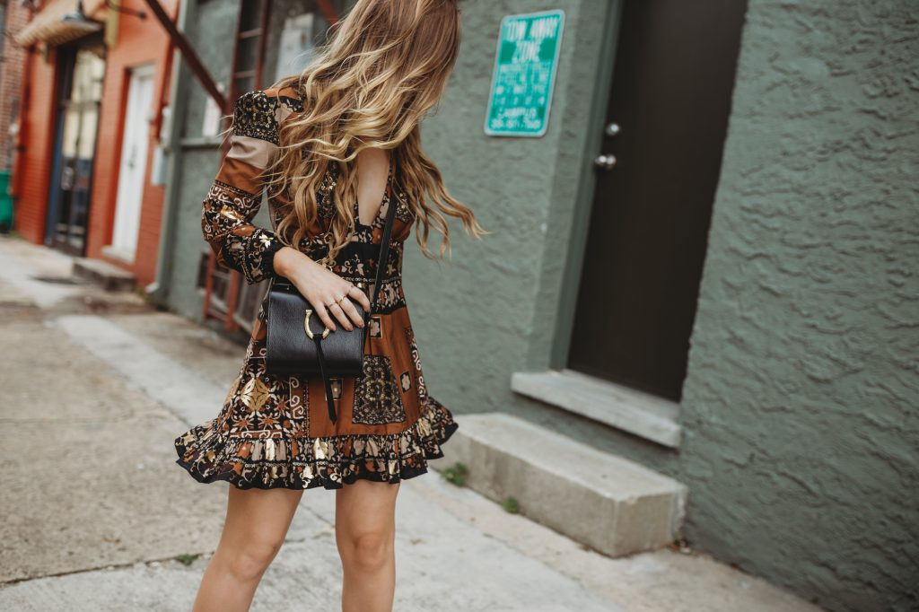 Shannon Jenkins of Upbeat Soles styles a spring boho outfit with a gold metallic dress, Schultz zip up booties, and Sancia black and gold crossbody
