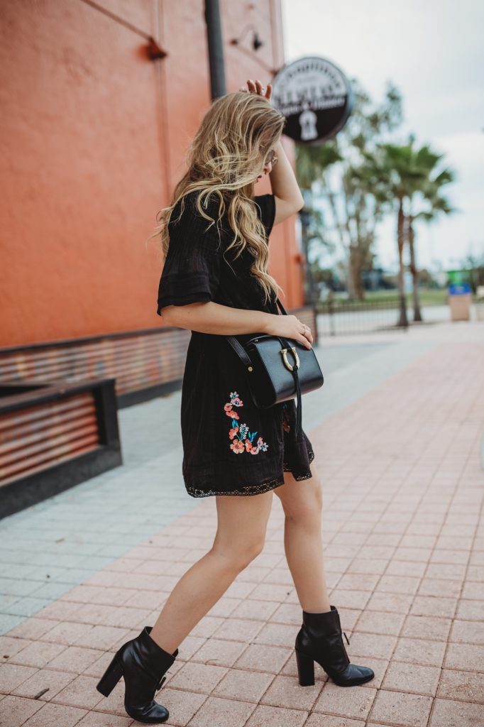 Shannon Jenkins of Upbeat Soles styles a spring boho outfit with a floral embroidered Free People dress, Schutz black booties, and Ray Ban aviators