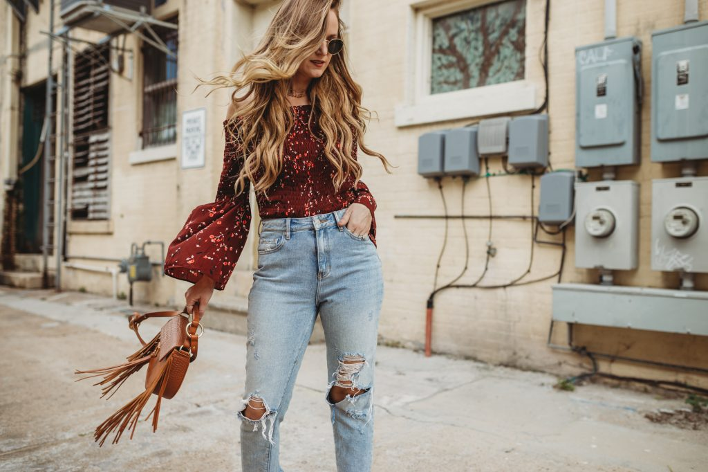 Shannon Jenkins of Upbeat Soles styles a 70's inspired outfit with Express bell sleeve top, high waisted mom jeans, Kelsie Dagger sandals, and fringe Sancia bag
