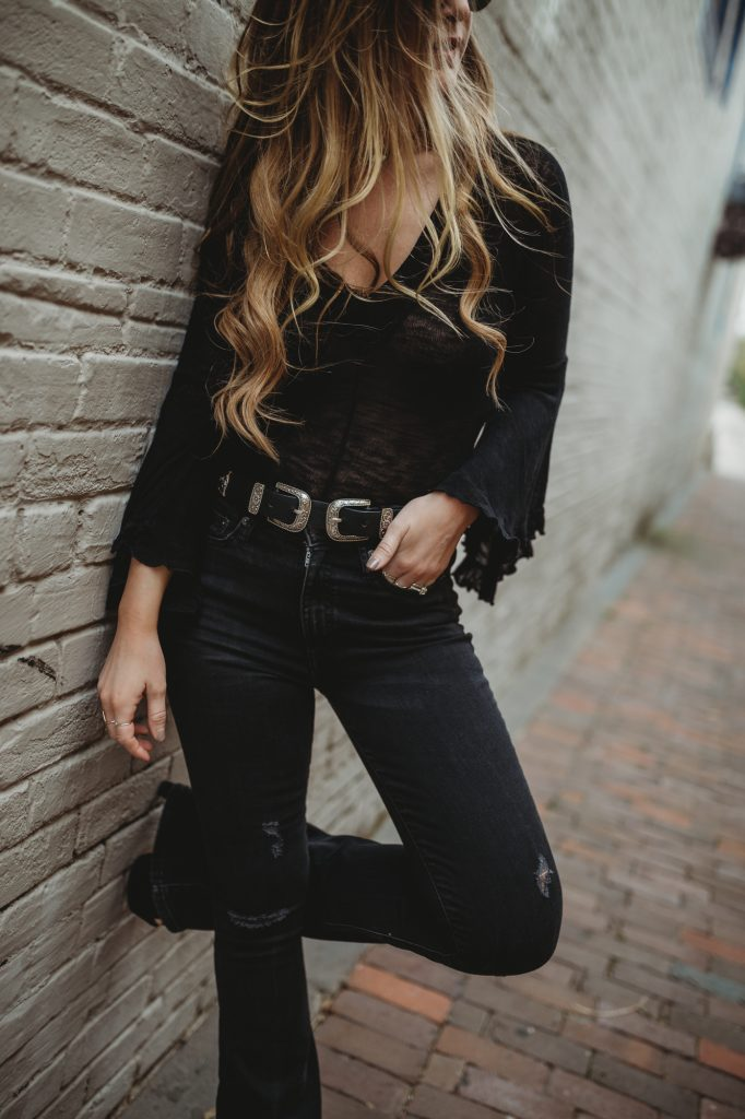 Shannon Jenkins of Upbeat Soles styles an edgy weekend concert outfit with a Free People bell sleeve top, American Eagle flared jeans, double buckle belt, and Sancia bag