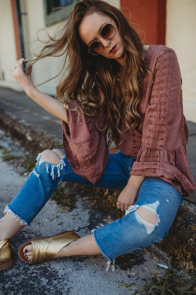 Shannon Jenkins of Upbeat Soles styles a boho bell sleeve outfit with an America Eagle eyelet top, distressed Levi jeans, gold Free People sandals, and Ray Ban aviators
