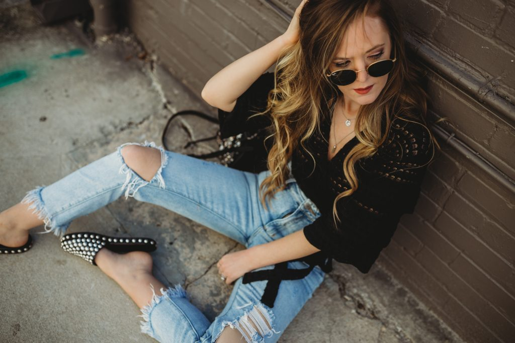 Shannon Jenkins of Upbeat Soles styles an edgy spring outfit styled with a Free People wrap crop top, high waisted mom jeans, Jefferey Campbell studded slides, and and round Ray Ban sunglasses