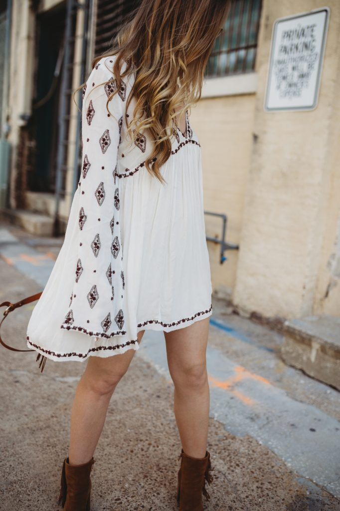Shannon Jenkins of Upbeat Soles styles a spring boho outfit with a flowy Free People dress, fringe Gianni Bini booties, Sancia fringe bag, and round Ray Bans
