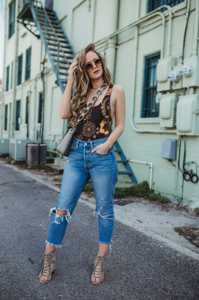 Shannon Jenkins of Upbeat Soles styles an easy weekend spring outfit with a Free People bodysuit, distressed Levi jeans, and lace up Jefferey Campbell wedges