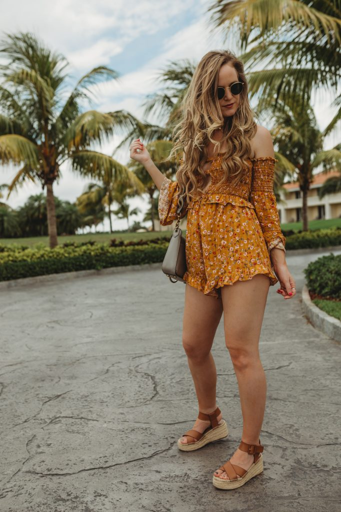 Shannon Jenkins of Upbeat Soles styles a cute vacation outfit with floral mustard romper from Tobi, Sole Society espadrille sandals, and Rebecca Minkoff guitar strap bag