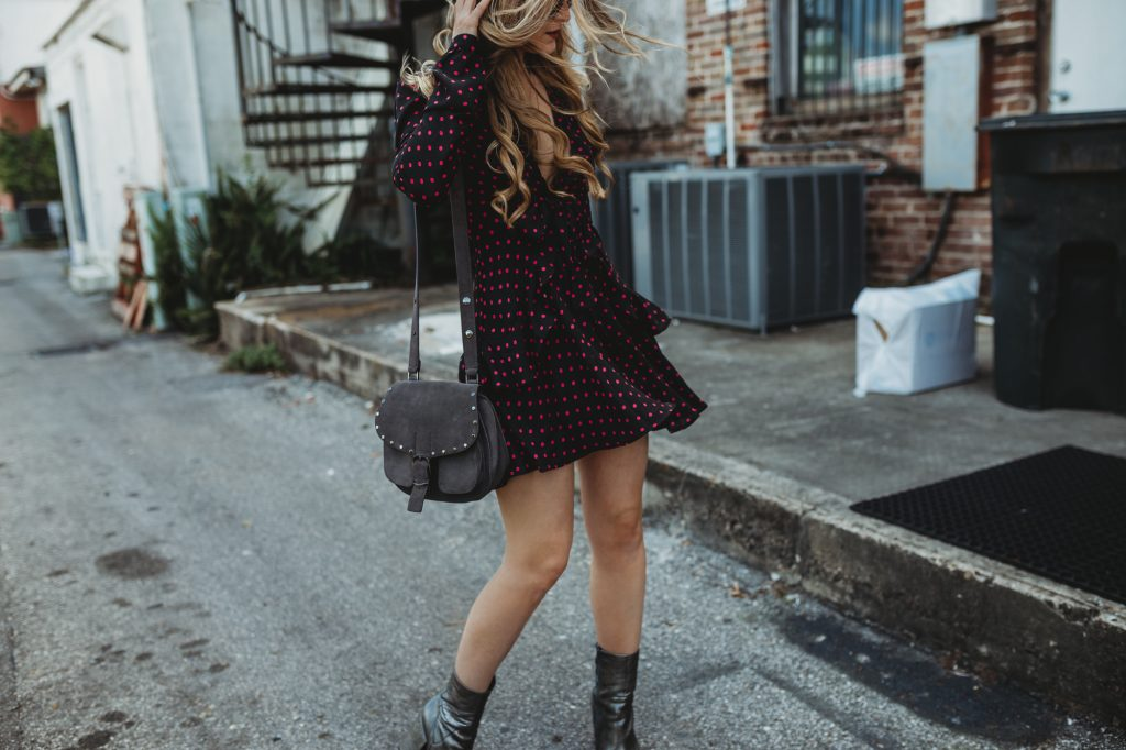 Shannon Jenkins of Upbeat Soles styles a spring date night outfit with plunging neckline polka dotted WAYF dress, metallic silver booties, Rebecca Minkoff bag, and Ray Ban Icon sunglasses