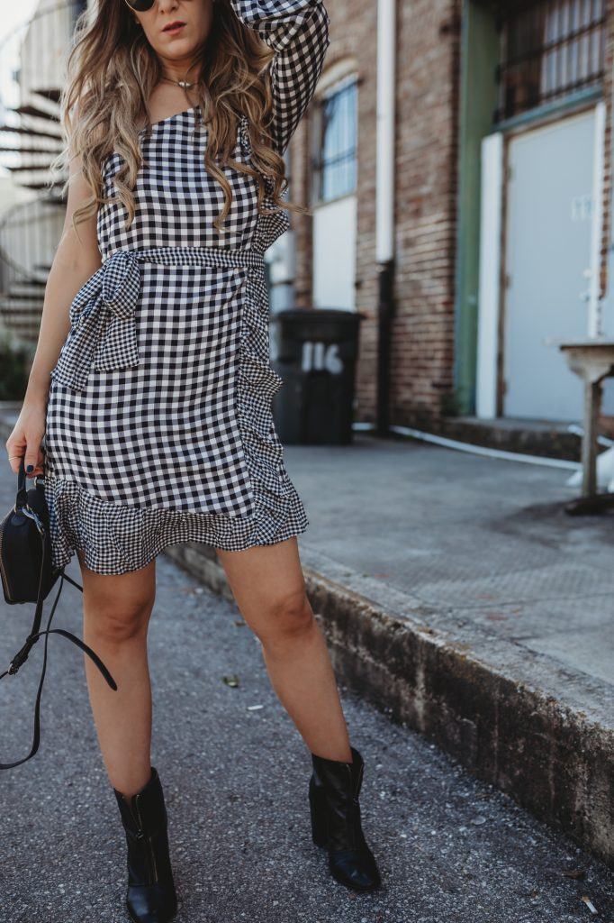 Shannon Jenkins of Upbeat Soles styles a spring edgy outfit with black and white ginham dress, Schutz booties, and Rebecca Minkoff crossbody
