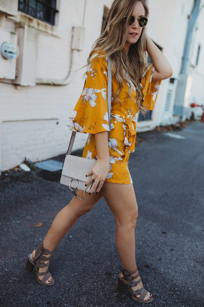Shannon Jenkins of Upbeat Soles styles a spring yellow floral romper from Chicwish with Dolce Vita buckle sandals, Kendra Scott choker, and Ray Ban Icon sunglasses