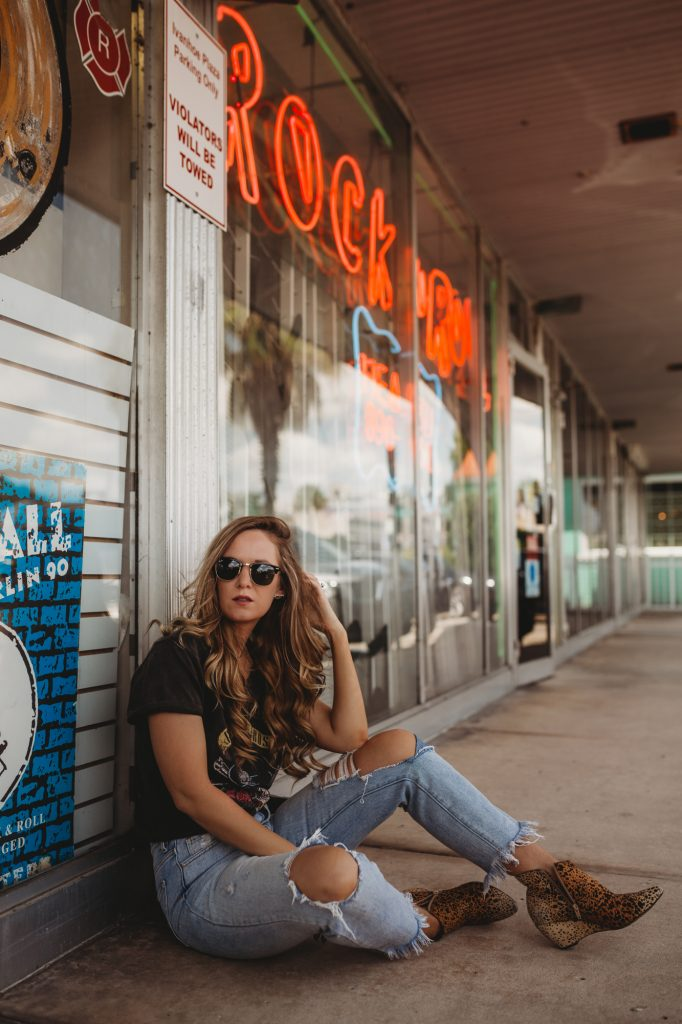Record store photoshoot, Shannon Jenkins of Upbeat Soles styles a rock n roll, edgy concert outfit with Guns N Roses vintage tee, high waisted distressed jeans, Matisse Nugent booties, and Ray Ban Clubmasters