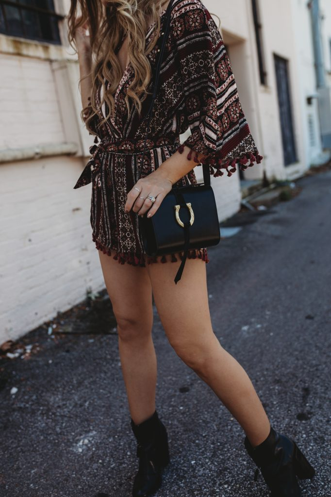 Shannon Jenkins of Upbeat Soles styles a boho spring outfit with Tobi tassel romper, Schutz booties, and round Ray Ban sunglasses
