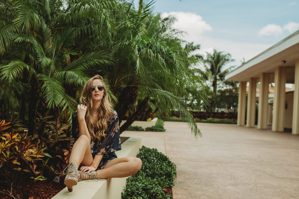 Shannon Jenkins from fashion blog Upbeat Soles styles a beach vacation outfit with a floral burn out romper from Tobi with Jeffrey Campbell lace up wedges and round Ray Ban Sunglasses