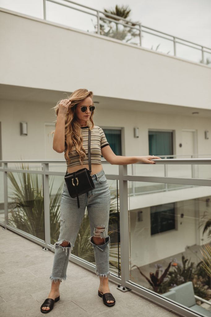 Shannon Jenkins of Upbeat Soles styles a casual edgy outfit with striped crop top, high waisted jeans, and Naturalizer sildes from Zappos