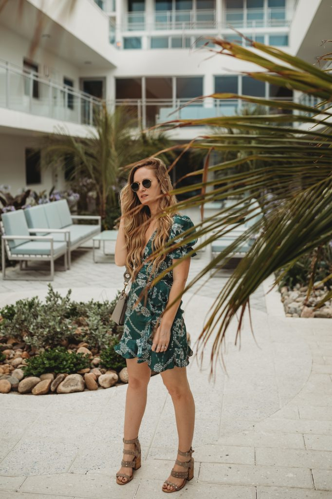 Shannon Jenkins of Upbeat Soles styles a beach vacation date night outfit with Shopbop green ruffled dress, Dolce Vita block heel sandals, and Rebecca Minkoff ring bag