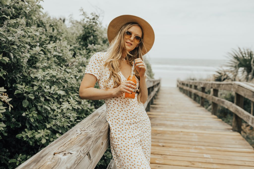 Shannon Jenkins from fashion blog Upbeat Soles styles a orange print Free People jumpsuit with platform espadrille sandals for a summer beach look