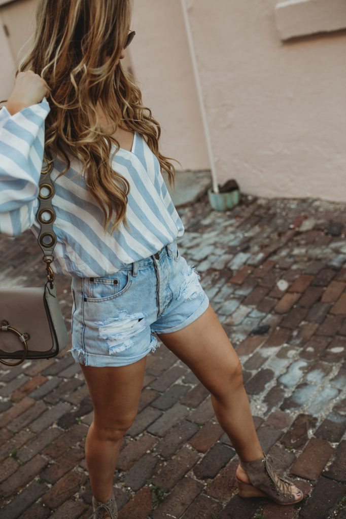 Shannon Jenkins of Upbeat Soles styles a casual weekend outfit with Tobi cropped bell sleeve top, high wasited distressed denim shorts and lace up Jefferey Campbell booties