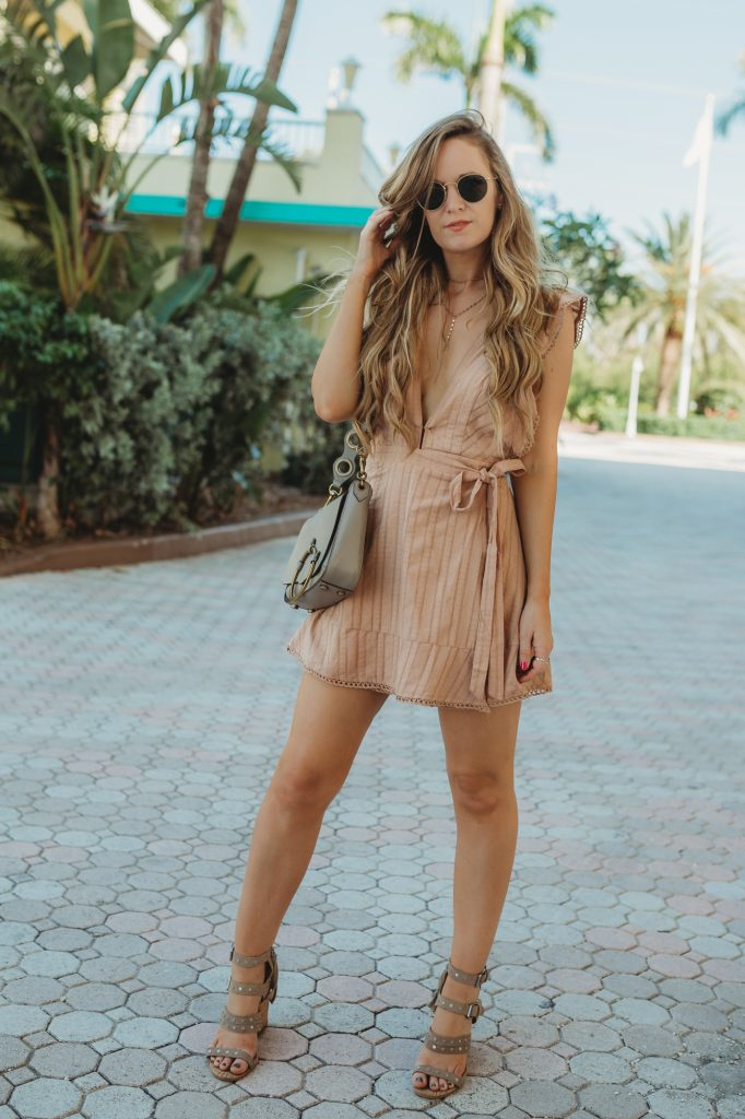 Shannon Jenkins of Upbeat Soles styles a spring date night outfit with a mauve plunging neckline dress, Dolce Vita studded sandals, and Rebecca Minkoff crossbody