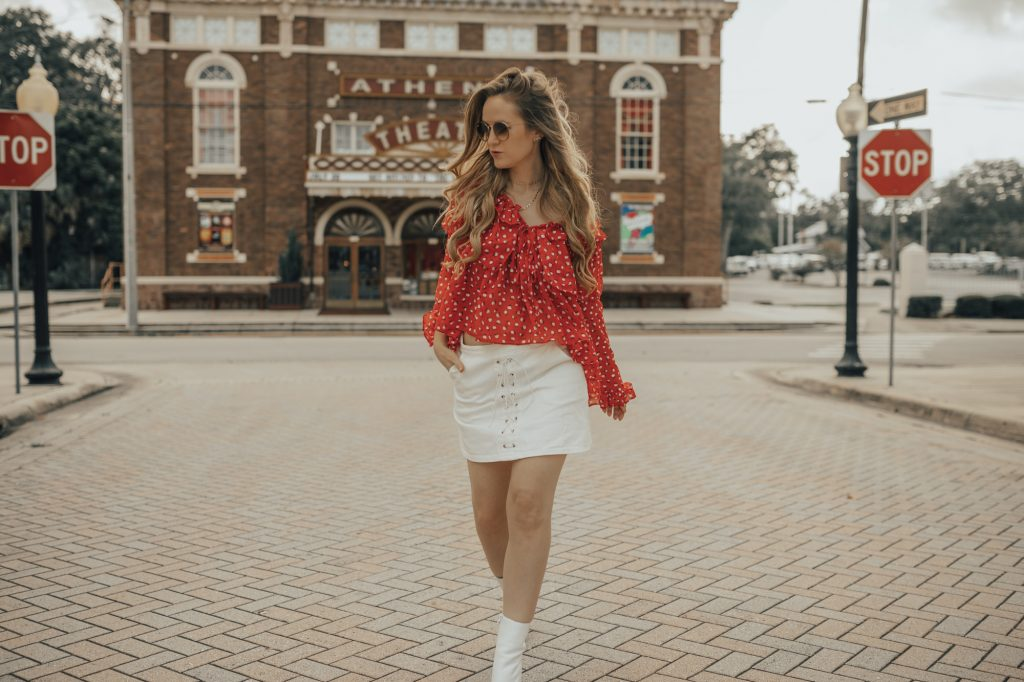 Shannon Jenkins of Upbeat Soles styles a retro summer outfit with red off the shoulder top, white lace up skit, and Jefferey Campbell white ankle booties
