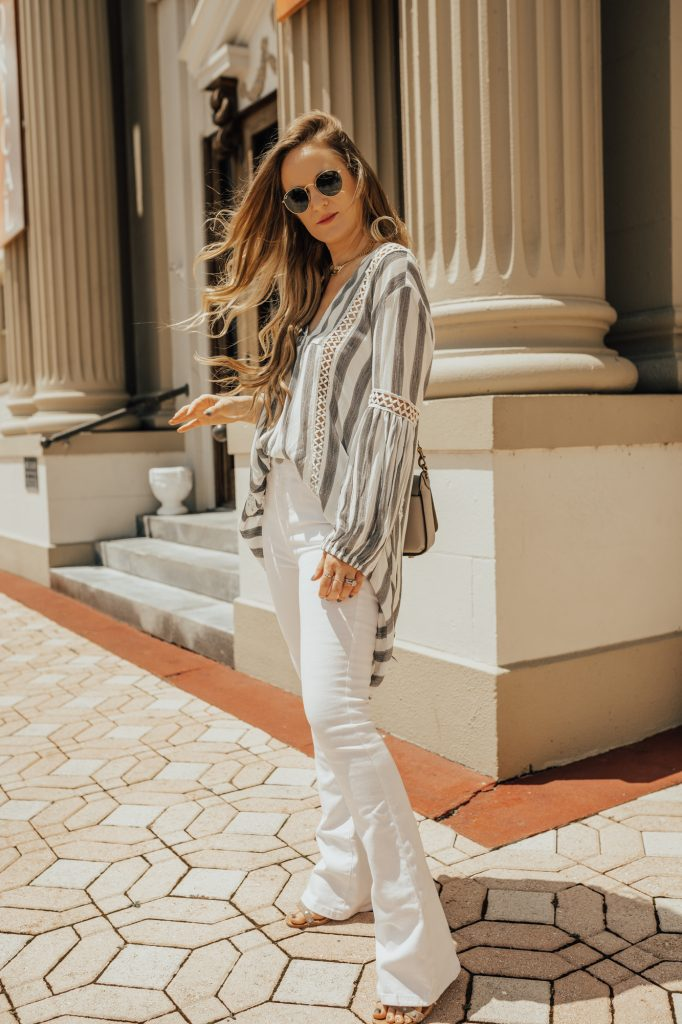 Shannon Jenkins of Upbeat Soles styles an edgy spring outfit with Chicwish striped high low top, white flared jeans, and Dolce Vita sandals
